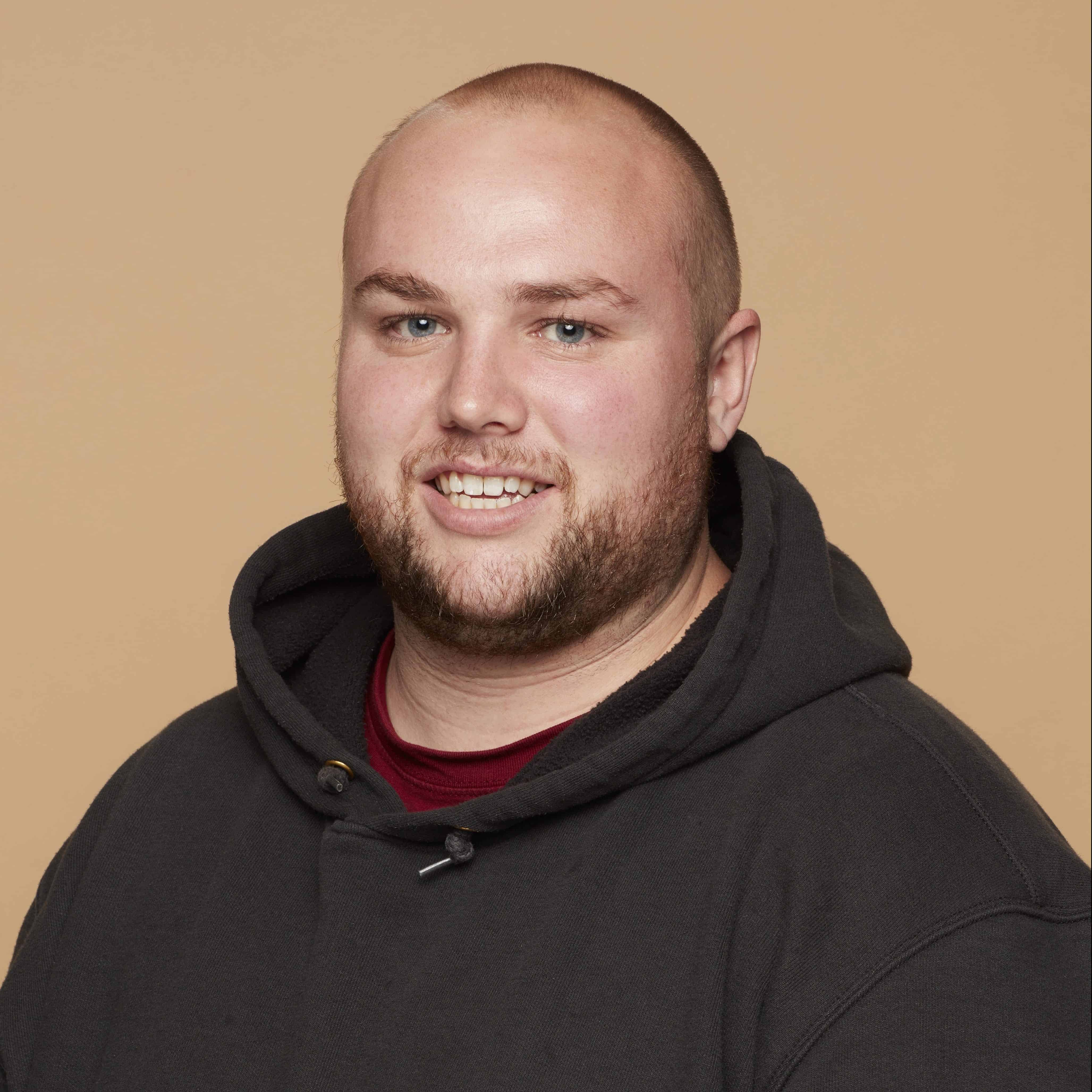 Charlie Grinnell smiles at the camera before an orange background wearing a black hoodie.