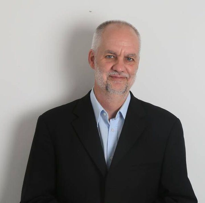 André Picard stands against a grey wall smiling at the camera. He is wearing a black suit and has his hands over his chest.